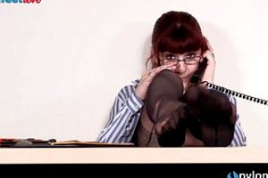 Redhead secretary in stockings and garter belt shows feet